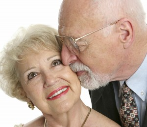 Every Day Sacred - closeup of a loving senior man gives his beautiful wife a kiss on the cheek
