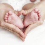Every Day Sacred - Newborn baby feet in the mother hands